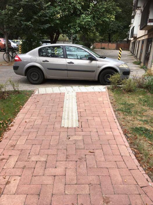 A képen egy parkoló autó látható, ami szabálytalanul a taktilis vezető sávon áll